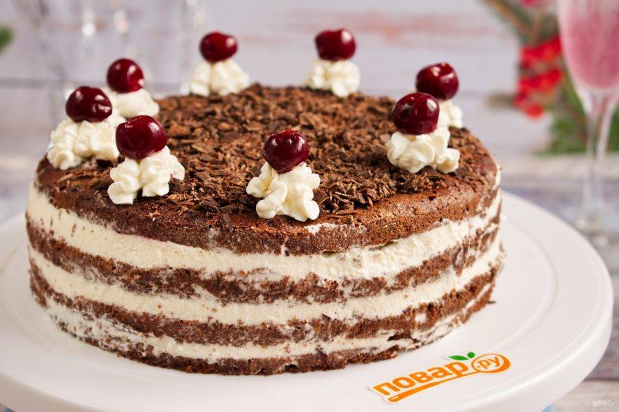 Сверху торт смажьте небольшим количеством крема, посыпьте тертым шоколадом. По кругу выдавите розочки из взбитых сливок. На каждую положите вишенку. Торт поставьте в холодильник на 2 часа.