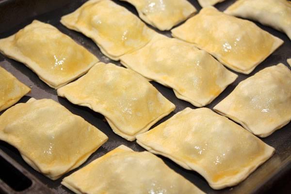 Противень смазываем масло и выкладываем пирожки, поверхность которых смазываем яйцом. Разогреваем духовку до 200 градусов.