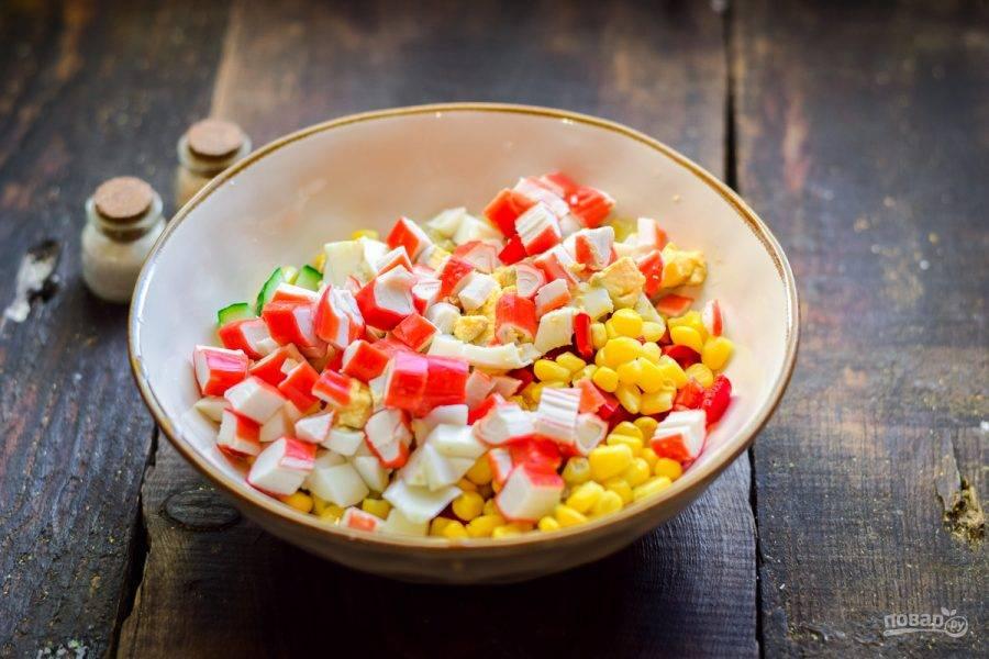 Нарежьте крабовые палочки, добавьте ко всем ингредиентам, всыпьте соль и перец.