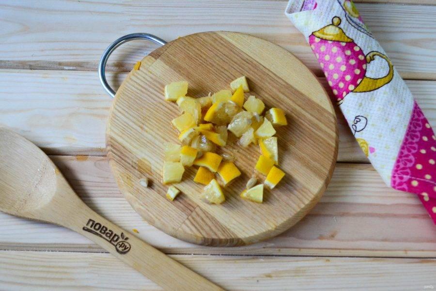 Пока варенье будет закипать, половинку лимона порежьте на небольшие кусочки (можно вместе с кожурой и косточками). Добавьте лимон в кастрюлю.