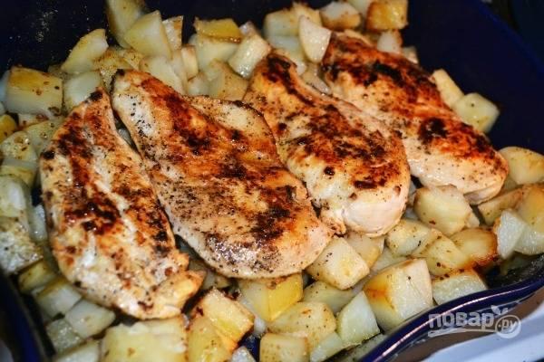 8.Достаньте из духовки картофель, снимите фольгу и выложите поверх него куриные грудки.