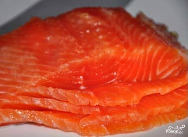 Берем красную рыбу. Под эту категорию рыбы подходят многие разновидности. Это может быть семга, кета, форель или кижуч. В общем, каждый берет рыбу по вкусу и возможностям. Нарезаем на тоненькие пластины и кладем на блин, посыпанный сыром.