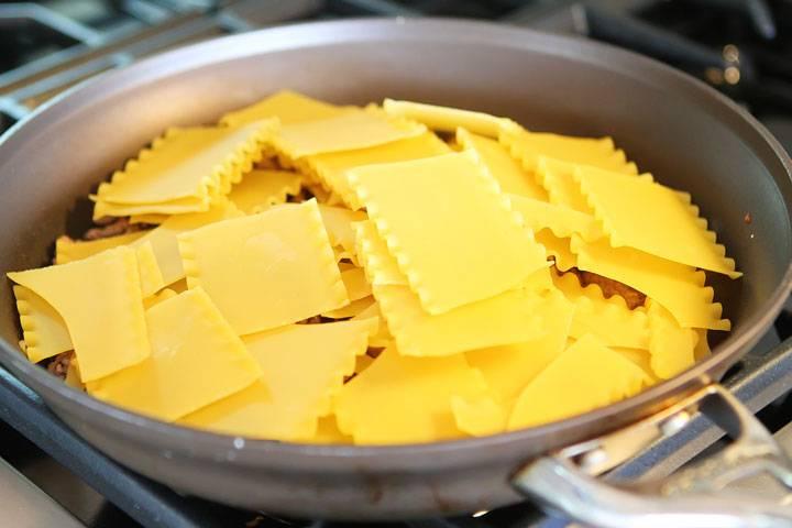 Добавьте нарезанные мелко сосиски и поломанные листы лазаньи.