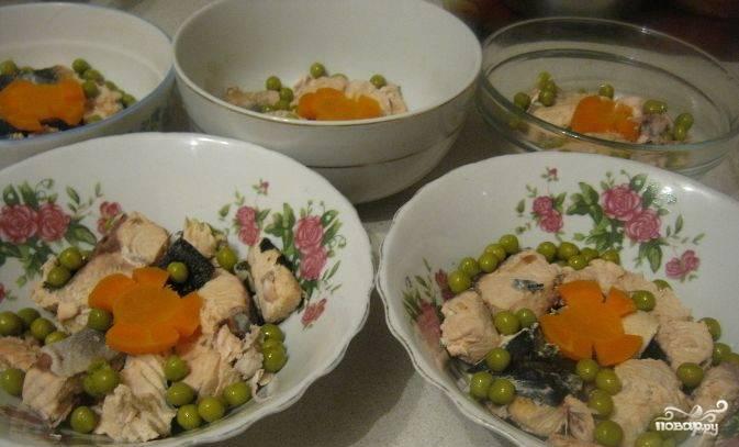 Как только вода закипит, достаньте лавровый лист. Иначе бульон будет горьким. Поварите на медленном огне ещё 2-2,5 часа. Затем достаньте всё из бульона, отставьте его в сторону, чтобы остыл. Сома разберите на мясо и кости. Кости выбрасываем. Морковь нарежьте, она будет в холодце. Выложите в мисочки для холодца мясо сома, морковь и зелёный горошек. Желатин разведите в воде, добавьте в бульон и немного поварите до полного растворения желатина. Залейте формочки.