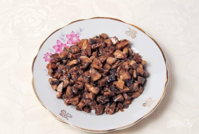 Лук обжарьте в разогретом масле около 5 минут. Затем добавьте к нему грибы. Тушите продукты на небольшом огне под крышкой в течение 15 минут. Всё посолите, а потом жарьте 10 минут без крышки.