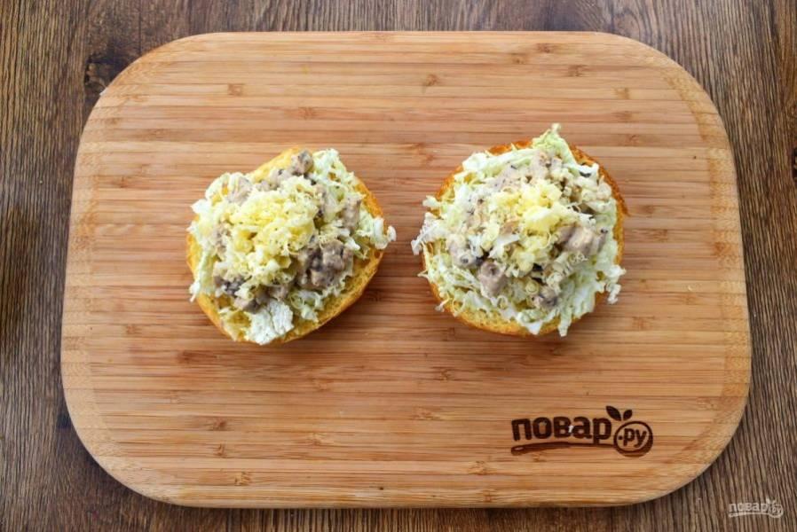 7. На верх булочки положите нашинкованную капусту, затем — кусочки грудки в соусе и посыпьте тертым сыром.