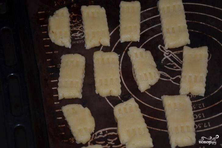 После того, как тесто затвердело, раскатайте его в пласт, вырежьте на нем фигурки. Можете раскатать тесто колбасками, нарезать их и приплюснуть каждый кусочек. Выпекайте получившееся печенье в духовке до румяной корочки.