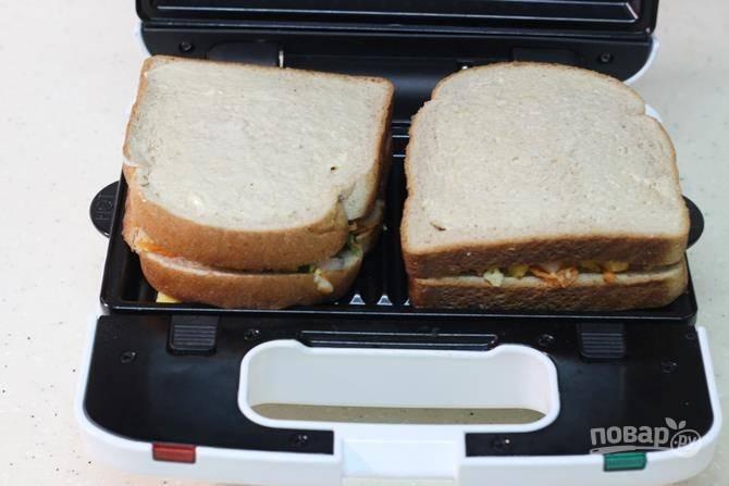 Разогрейте бутербродницу, накройте начинку вторым кусочком хлеба и запеките примерно минуту-полторы.