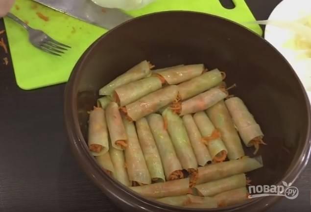 5. Морковку закладываем на капустный лист с самого узкого края, чтобы она немного выглядывала по бокам. Закручивать голубец надо плотно. Выложите все голубцы в глубокую емкость, сверху заложите целыми капустными листами.