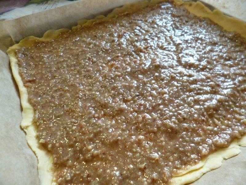 Часть теста раскатайте и отправьте в духовку на 5 минут, чтобы подрумянилась. Противень застилаем бумагой для выпечки, выкладываем сырой корж, на него кладем половину начинки, разравниваем.