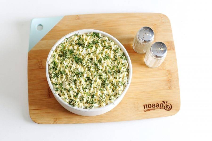 Посолите и поперчите яйца по вкусу. Сверху сделайте сеточку из майонеза и украсьте салат зеленью.
