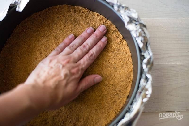 Печенье нужно измельчить в крошку в блендере. Потом добавляем туда мягкое сливочное масло, шепотку соли и корицу. Все тщательно перемешиваем и выкладываем массу на дно формы, утрамбовывая. Запекаем пласт при 180 градусах 10 минут, достаем, а температуру в духовке уменьшаем до 160.