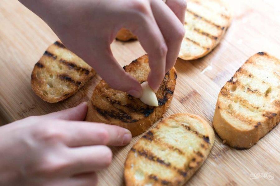 Первым делом батон нужно подогреть на гриле без масла, чтобы образовались корочки и легкие подпалины. Затем хорошенько натрите хлеб чесноком.