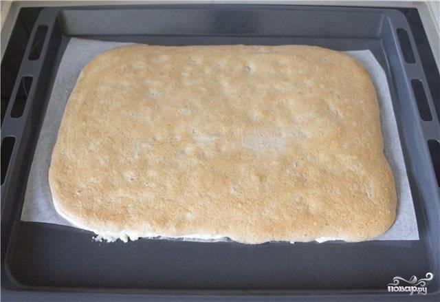 5. Достаньте противень из духовки и сразу же переверните корж на чистое полотенце. Можно его предварительно присыпать сахарной пудрой.