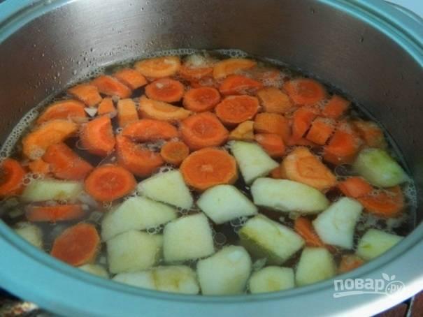 Через пару минут добавляем морковь и яблоки. Варить необходимо до готовности морковки.