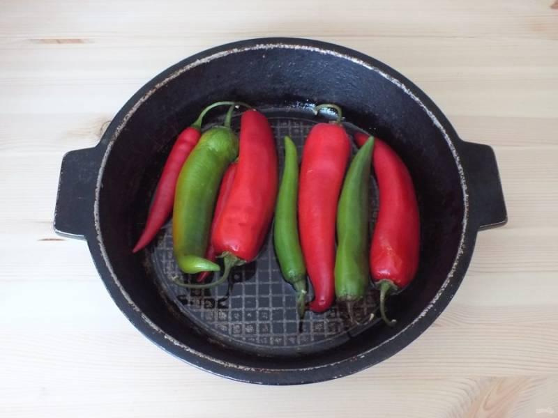 Возьмите широкую жаровню. Налейте в нее масло и разогрейте, после опустите вымытые и высушенные перцы. Закройте крышкой, убавьте огонь.