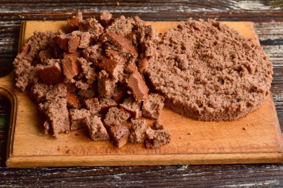 Разрежьте готовый бисквит пополам. Одну часть нарежьте кубиками.