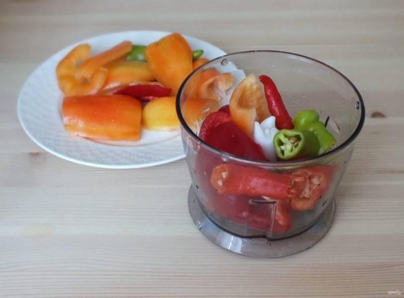 Оба вида перца измельчите в блендере или мясорубке. У острого перца предварительно удалите плодоножку, семена не удаляйте.