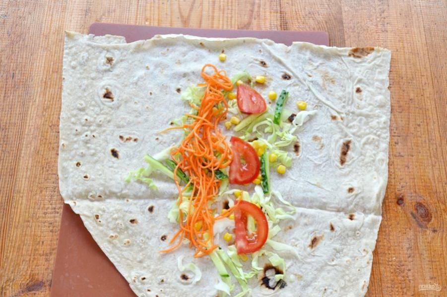 Распределите ровным слоем овощи - капусту, огурец, морковь, немного кукурузы, помидор.