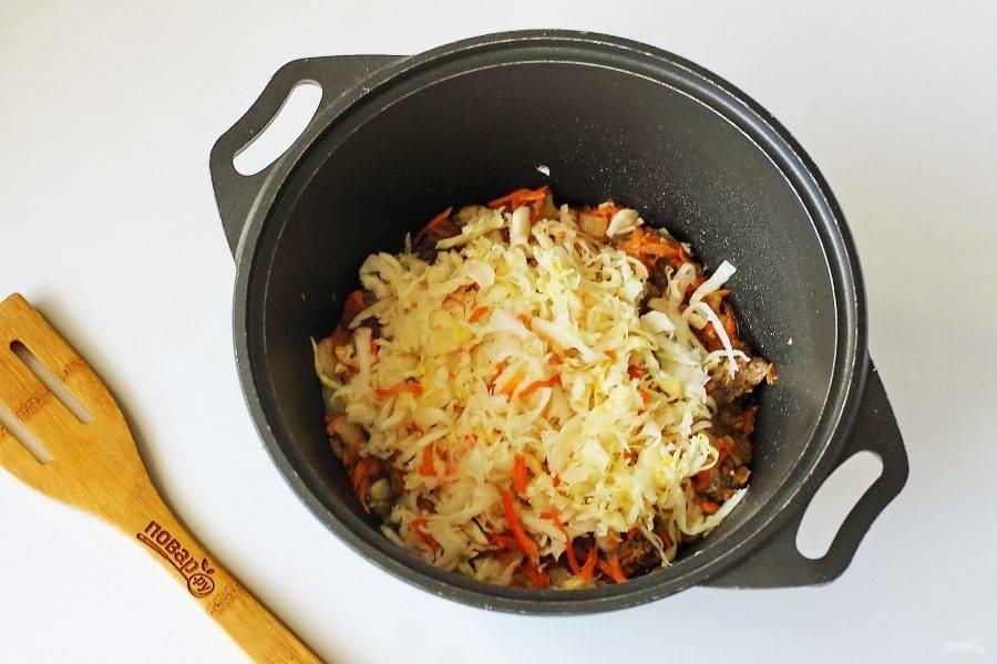 Обжарьте овощи до мягкости и добавьте квашеную, отжатую от сока, капусту. Если капуста сильно кислит, то предварительно можно промыть ее под холодной водой.