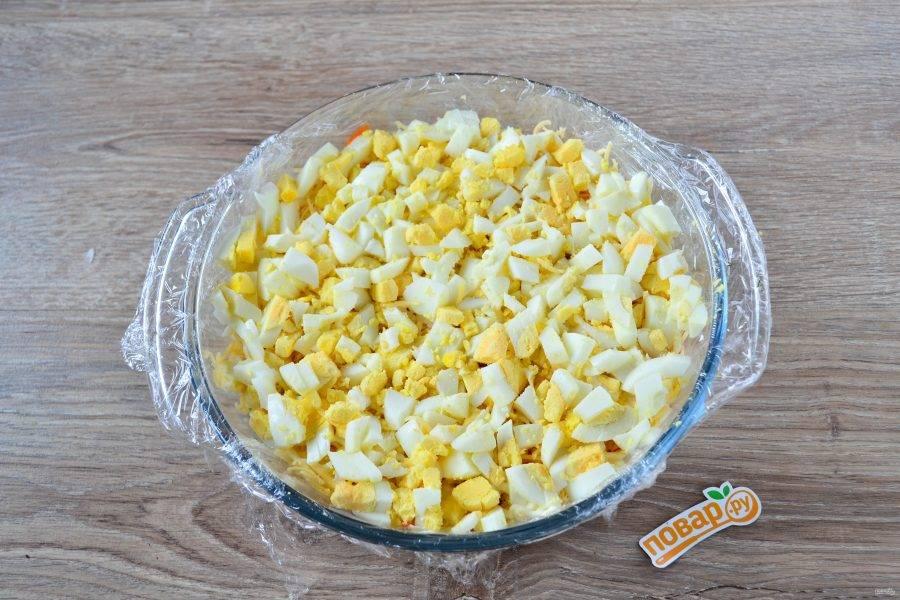 Яйца порежьте кубиком (или натрите на мелкой терке, как остальные продукты) и выложите следующим слоем. Сверху покройте сеточкой майонеза.