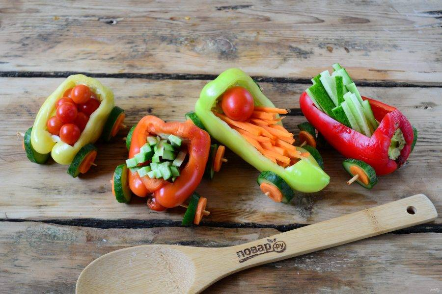 Наполните вагончики из сладкого перца  помидорами черри, соломкой из моркови и огурца.