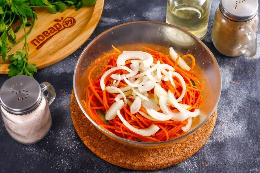 Очистите и промойте лук, половину овоща нарежьте полукольцами и добавьте в емкость вместе с морковью по-корейски.