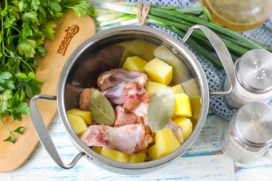 Части курицы промойте в воде, выложите в кастрюлю. Очистите от кожуры картофель, морковь и репчатый лук, промойте в воде. Картофель нарежьте средними кубиками и отправьте в емкость курице. Добавьте лавровые листья, соль и влейте воду. Поместите емкость на плиту и доведите до кипения, снимите образовавшуюся пену. Затем убавьте нагрев и отварите в течение 10 минут.