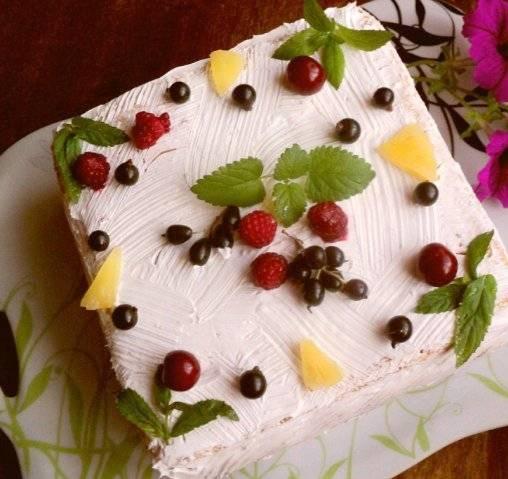 5. Для последнего коржа сделаем белый крем-глазурь. Для этого взбиваем сливки с сахарной пудрой. Если сливки жирные, они быстро увеличатся в объеме. Взбиваем до появления пиков. Смажем торт сверху и по бокам, украсим фруктами и отправим в холодильник. Подаем холодным через 6-8 часов. Готово!