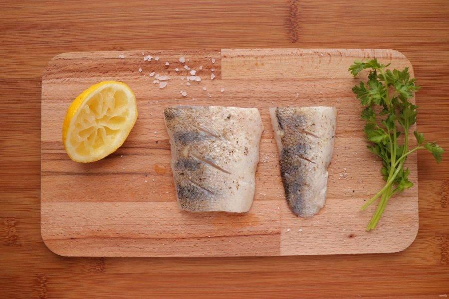 На каждом кусочке филе рыбы сделайте надрезы. Посолите, поперчите и сбрызните рыбу лимонным соком.