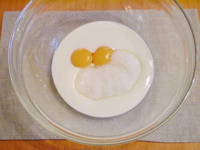 В глубокую посуду добавляем: кефир комнатной температуры, желтки (предварительно отделенные от белков) и сахар. Всё тщательно взбиваем венчиком.