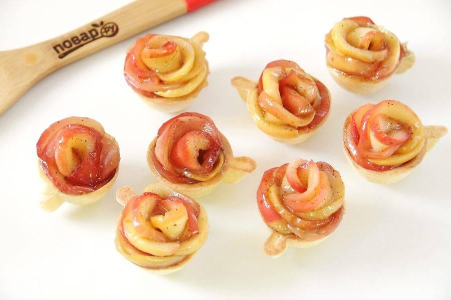 6. В каждую тарталетку уложите яблочные дольки по кругу внахлест друг на друга. Должны получиться своеобразные яблочные розочки. Полейте яблоки сверху остатками меда с корицей.
