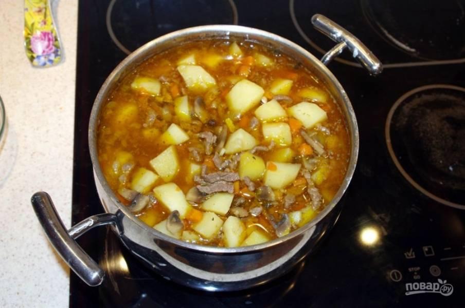 10. Тушим на среднем огне и постоянно помешиваем. Для этого блюда идеально подойдет картофель, который быстро разваривается, в результате чего получается не просто мясо, тушенное с грибами, а своего рода жаркое с мясом и грибами.