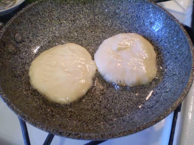 В горячее масло выкладываем ложкой небольшое количество теста, жарим оладьи с двух сторон до румяной корочки.