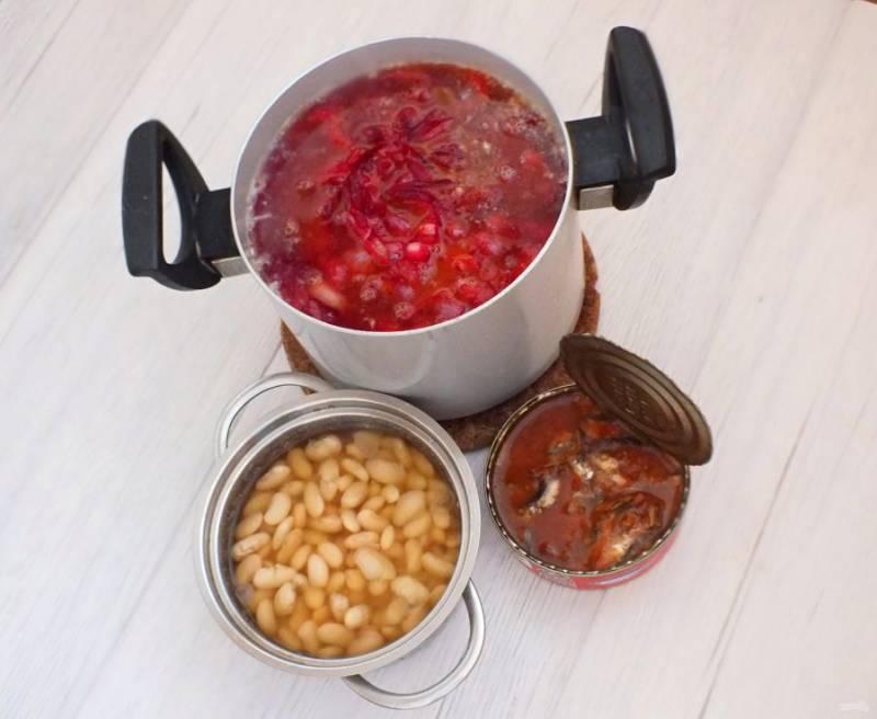 В кастрюлю с картофелем и капустой переложите обжаренные овощи со свеклой. Перемешайте. Добавьте фасоль и кильку в томате, перемешайте.