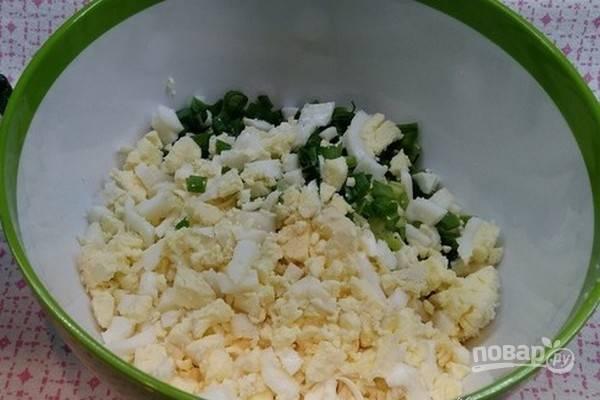 Перья зеленого лука мелко нарежьте. Нарежьте 3 желтка и 1 яичный белок, а 2 белка оставьте для украшения салата.