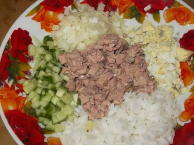 В салатницу выкладываем рис, также добавляем измельченную печень трески, огурец, лук и яйца.