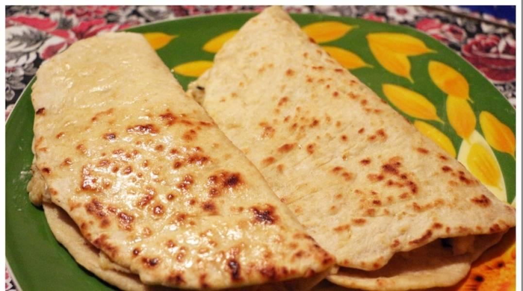 Разделите тесто на небольшие кусочки и раскатайте их в лепешки (сделайте пару проколов, чтобы тесто не вздулось при жарке). Жарим лепешки на сухой сковороде, обжаривая с обеих сторон. После чего смазываем горячую лепешку растопленным сливочным маслом, намазываем на одну сторону начинку, а второй стороной накрываем. Приятного аппетита!