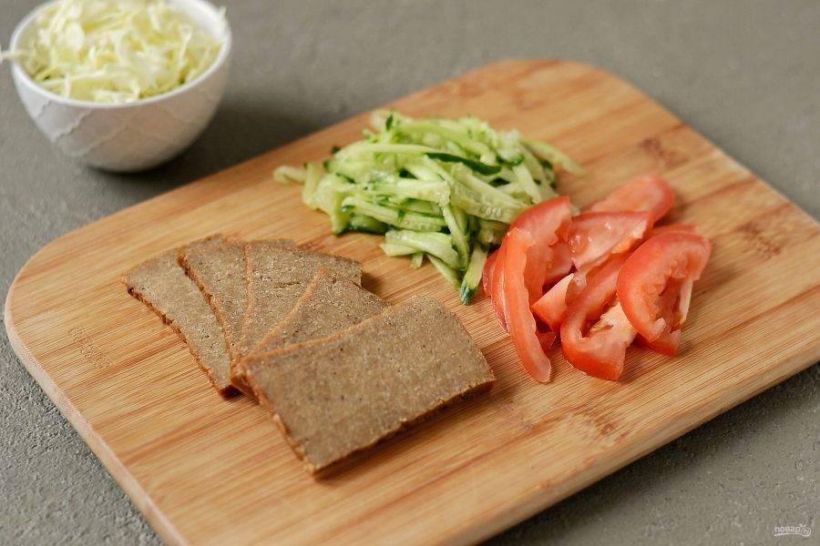Сейтан нарежьте пластинами, помидоры дольками, капусту тонко нашинкуйте, а огурец порубите соломкой.