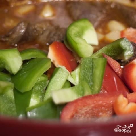 10. Через час и десять минут добавьте в утятницу нарезанные кубиками болгарский перец и картошку (картошку предварительно очистите). Запекайте еще 30 минут.