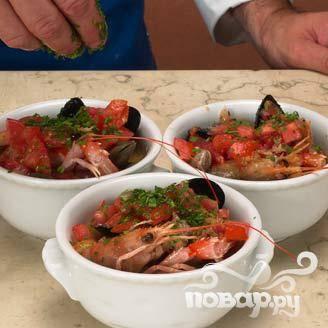 Обложить горшочки с морепродуктами нарезанными помидорами и оливками (без косточек), посыпать петрушкой. Залить бульоном. Выпекать в духовке при температуре 180 ° С в течение 5 минут. Подавать с кусочками хлеба.