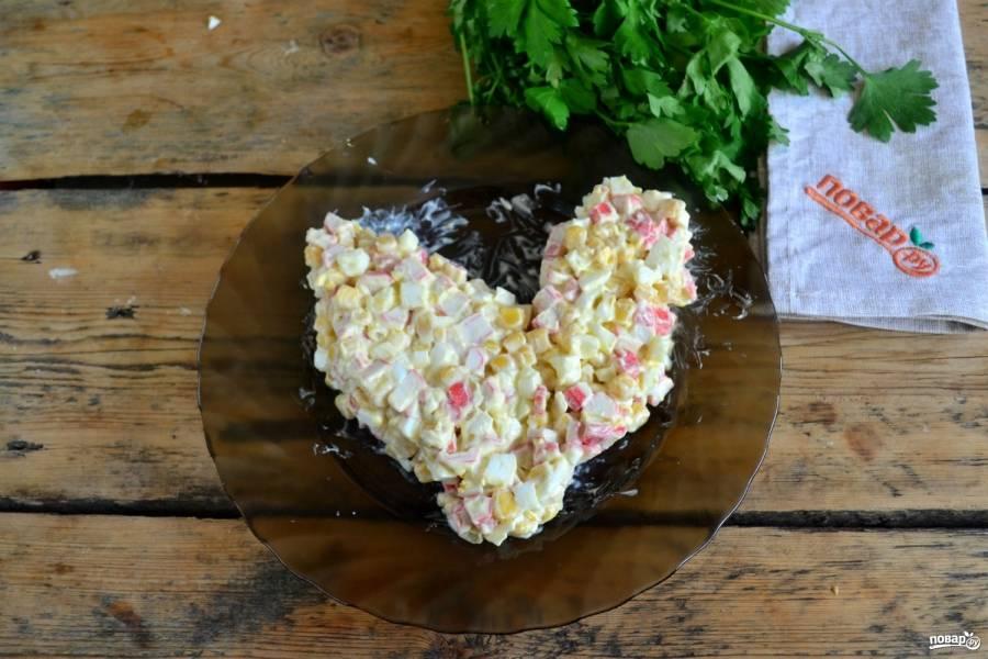 На плоскую тарелку выложите полученный салат, придайте ему форму петушка, как показано на фото.