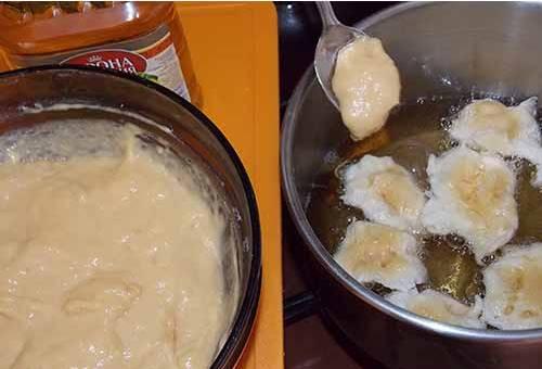 Заливаем в кастрюлю подсолнечное масло. Начинаем жарить его, смачиваем в нем столовую ложку. Этой ложкой выхватываем тесто из миски и опускаем в кастрюлю.