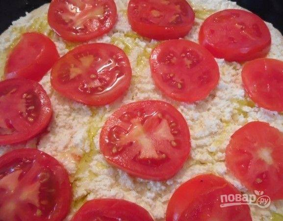 Сверху выложите кружки помидоров. Сбрызните их оливковым маслом.