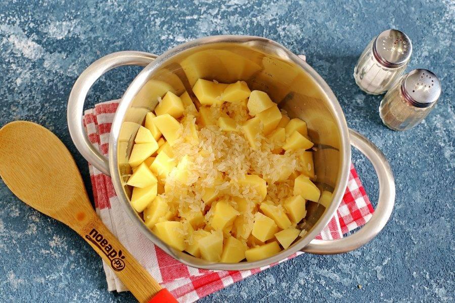В кастрюльку выложите нарезанный кубиками картофель и промытый рис.