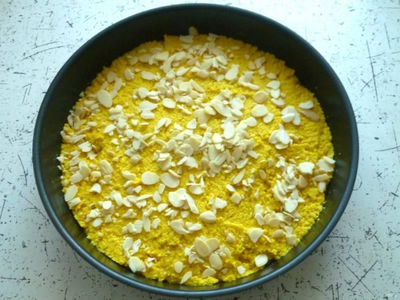 Форму для выпекания (24-26 см) при необходимости смажьте небольшим количеством оливкового масла. Для этого удобно использовать бумажные салфетки. Выложите тесто и разровняйте его лопаткой. Сверху посыпьте миндальные лепестки и выпекайте 40 минут при 180°. Готовность можно проверить зубочисткой – она должна выходить сухой.