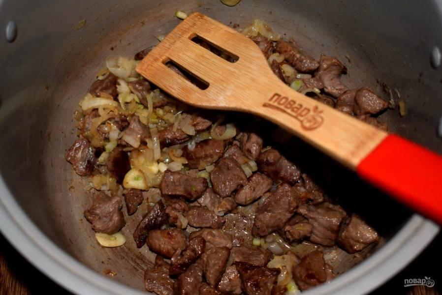 Добавьте измельченный лук и чеснок, обжаривайте в течение 3 минут.