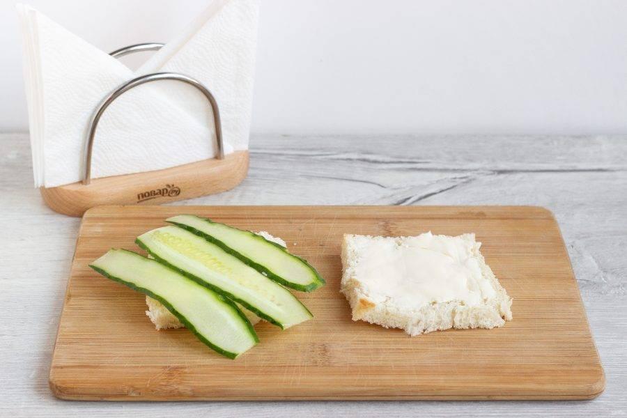Все тосты с одной стороны смажьте сливочным сыром, на сыр выложите пластинки огурцов.
