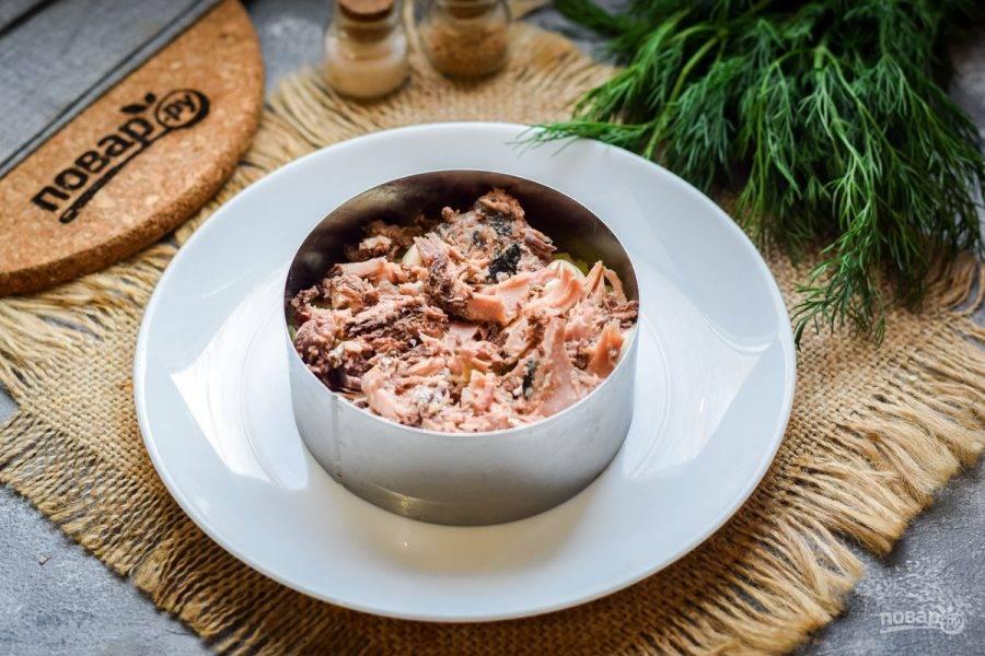 Тунец откройте и слейте сок, разомните рыбу вилкой. Выложите тунец поверх картофеля.