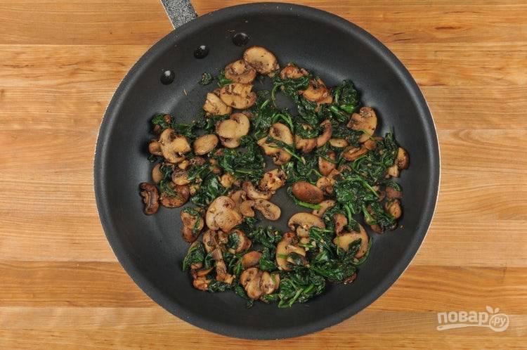 3. В сковороде разогрейте масло. Обжарьте в нём шампиньоны с итальянскими травами до выпаривания воды и появления коричневого цвета, около 7 минут. Затем добавьте красный перец с чесноком, помешивая подогрейте ингредиенты 30 секунд. Потом отправьте в сковороду шпинат. Готовьте ещё 3 минуты. В конце добавьте соль и чёрный перец.